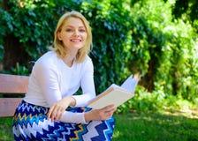 放松在庭院阅读书的妇女愉快的微笑的白肤金发的作为断裂 女孩坐放松与书,绿色自然的长凳 库存照片