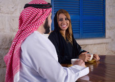 放松在庭院饮用的茶的阿拉伯夫妇 免版税库存照片