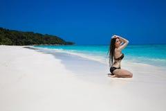 放松在异乎寻常热带的黑比基尼泳装的美丽的性感的妇女 免版税库存照片