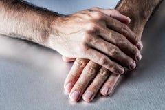 放松在彼此的男性手平展等待或听 图库摄影