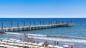放松在拥挤海滩的人们 免版税库存照片