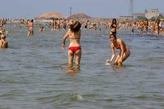放松在拥挤海滩的人们 库存照片