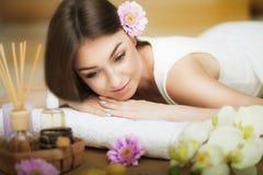 放松在按摩桌上的一个健康女孩 在温泉的做法前 男按摩师去按摩他的  机体关心英尺健康温泉水妇女 皮肤c 免版税库存照片