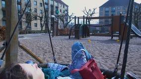 放松在摇摆在城市操场,童年记忆,自由,休息的妇女 股票视频