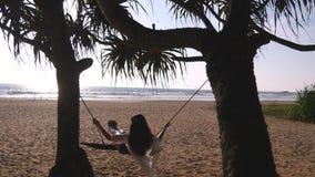放松在摇摆的泳装和衬衣的年轻愉快的妇女在热带海洋海滩 美丽的女孩坐摇摆和 股票录像