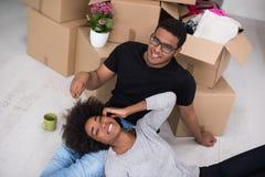 放松在新房里的非裔美国人的夫妇 库存图片