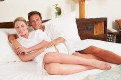 放松在旅馆客房佩带的长袍的夫妇 库存照片