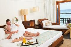 放松在旅馆客房佩带的长袍的资深夫妇 库存照片