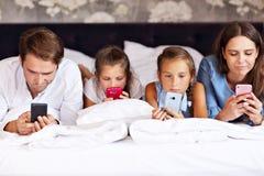 放松在旅馆客房的愉快的家庭 库存图片