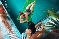 放松在旅馆游泳池的亭亭玉立的年轻女性朋友顶视图  免版税库存图片