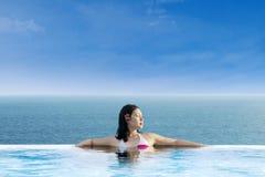 放松在无限游泳池的可爱的妇女 库存照片