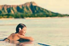 放松在无限游泳池的微笑的妇女 图库摄影