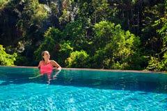 放松在无限游泳池的豪华温泉旅馆里的妇女 免版税库存图片