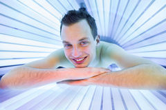 放松在日光浴室的英俊的年轻人 免版税库存图片