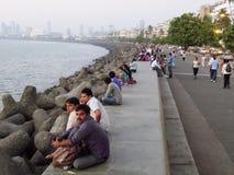 放松在日落期间的人们在海洋驱动在孟买 免版税库存照片