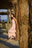 放松在日落的海滩的美丽的妇女 免版税库存照片