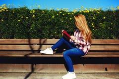 放松在春天公园的迷人的女孩,当读的书时 免版税库存照片