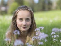 放松在春天草甸的美丽的女孩 免版税库存照片
