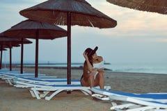 放松在晚上的海滩的年轻俏丽的夫人在夏天户外背景的遮阳伞休息室附近 库存图片