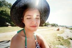 放松在晴朗的海滩,夏天的时髦的帽子的愉快的逗人喜爱的妇女 库存照片