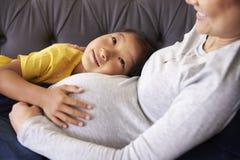 放松在有女儿的沙发的怀孕的母亲 免版税库存图片