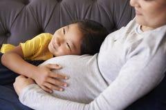放松在有女儿的沙发的怀孕的母亲 免版税库存照片