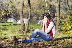 放松在有她的狗的秋天公园的病的妇女 库存照片