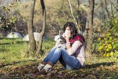 放松在有她的狗的秋天公园的病的妇女 免版税库存照片
