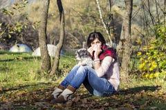 放松在有她的狗的秋天公园的病的妇女 免版税库存图片