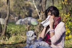 放松在有她的狗的秋天公园的病的妇女 图库摄影