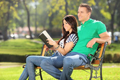 放松在有她的男朋友的一个公园的女孩 免版税库存图片
