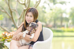 放松在有小狗哈巴狗狗的公园的逗人喜爱的亚洲女孩拥抱 免版税库存图片