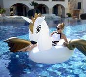 放松在有巨大的双的豪华游泳池度假旅馆里的妇女 免版税库存图片