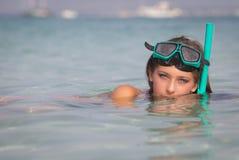 放松在有废气管和面具的海的少妇 免版税库存图片