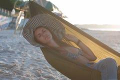 放松在有晒日光浴在度假的帽子的吊床的妇女 以落日的海为背景 库存照片