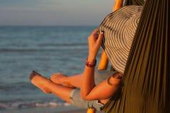放松在有晒日光浴在度假的帽子的吊床的妇女 以落日的海为背景 图库摄影