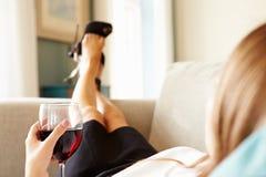 放松在有杯的沙发的妇女酒在工作以后 库存照片