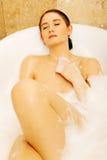 放松在有泡影的浴缸的妇女 图库摄影