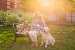 放松在有爱犬的庭院里的家庭 免版税库存照片