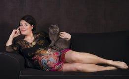 放松在有猫的一个沙发的孕妇 库存图片