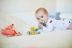 放松在有玩具的托儿所的女婴 免版税库存照片