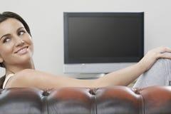 放松在有电视的沙发的妇女在背景中 库存照片