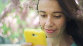 放松在有电话的春天开花的公园的年轻人微笑的美丽的旅游妇女 股票录像