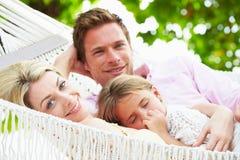 放松在有睡觉的女儿的海滩吊床的家庭 免版税图库摄影