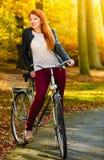 放松在有自行车的秋天公园的秀丽女孩,室外 免版税库存照片