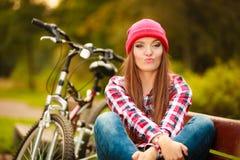 放松在有自行车的秋季公园的女孩 库存照片