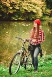 放松在有自行车的秋季公园的女孩 免版税库存图片