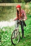 放松在有自行车的秋季公园的女孩 图库摄影