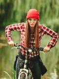 放松在有自行车的秋季公园的女孩 免版税图库摄影