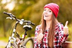 放松在有自行车的秋季公园的女孩 免版税库存照片